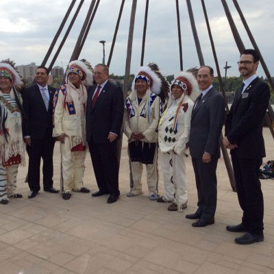 Group of men both Indigenous and white some in traditional native attire of the plains including headdresses and other men in business suits with metal teepee structure in behind