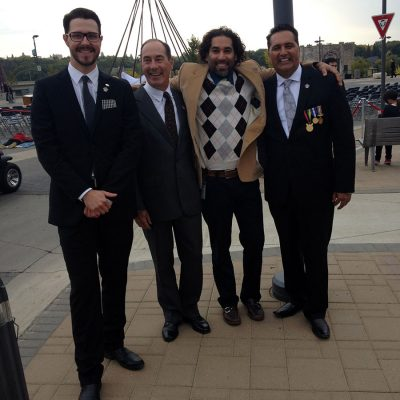 Four middle aged men stand in front of camera with metal teepee frame structure behind