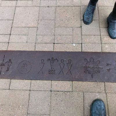 Metal strip on ground with etched in figures. The strip is between interlocking stones. On either side are the feet of metal statues, top in colonial boots, bottom in traditional native boots with beadwork tracings.