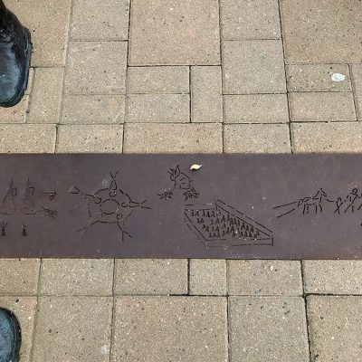 Metal strip on ground with etched in figures. The strip is between interlocking stones.